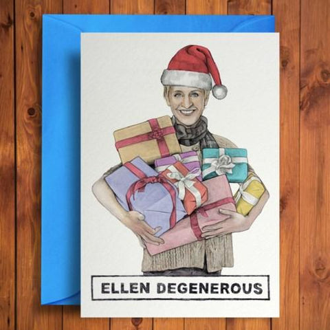 "Card on top of sky blue envelope. Card features illustration of Ellen Degeneres in a Santa hat holding a pile of presents. Text at bottom of card reads: ""Ellen Degenerous."" White background."