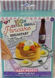 "Package of ""100% Extra Small Pancake Breakfast"" shows completed craft with stack of pancakes and 2 sunny side up fried eggs on plate and placemat, utensils, and bottle of syrup."