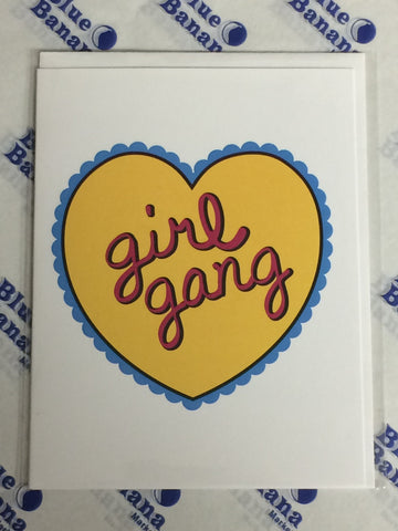 "Front of card, white with a yellow heart in the center. Heart is surrounded by a blue fringe, and in the center of it are the words ""girl gang"" in red script."