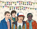 "Front of card with illustration of kids from Stranger Things standing under multicolored string lights. Text reads ""Have A Strange Birthday!"""