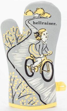 "Grey oven mitt with black, white, and yellow illustration of a little blonde girl with hair ribbons, in a skirt, riding a bike down a path away from her rural home. Text above her head reads ""hellraiser."""