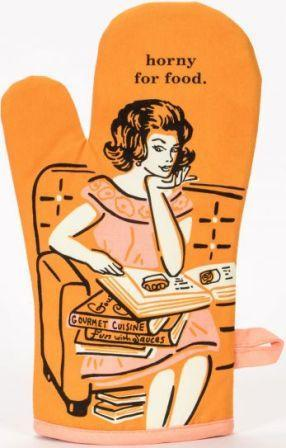 "Orange oven mitt with retro illustration of glamorous housewife seated on a couch with a pile of cookbooks, gazing at the one open in her lap. Text above her head reads ""horny for food."""