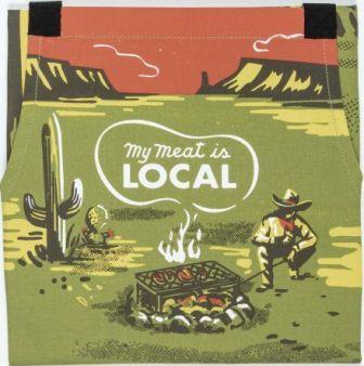 "Front of apron shows cowboy cooking steaks in the desert. Olive green with burnt sierra sky and accents and yellow accents. White smoke from fire circles the words ""My Meat is Local."""