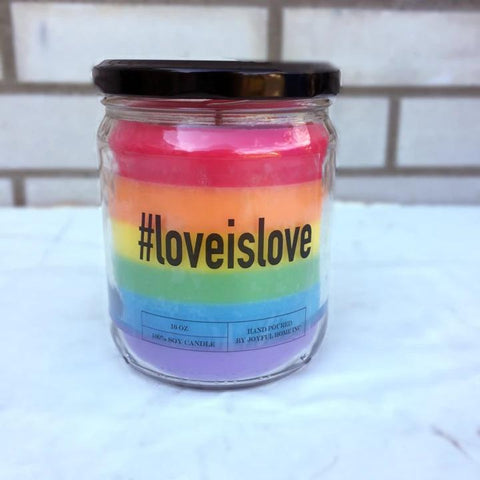 "Rainbow Pride candle in glass jar with black lid. Text on jar reads ""#loveislove."""