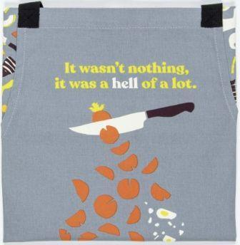 "Front of apron, grey with illustration of knife slicing a carrot. Above the knife the sentence ""It wasn't nothing, it was a hell of a lot."" Words are yellow, except for ""hell,"" which is white."