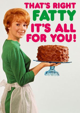 "Front of card with red haired woman in green dress and white apron smiling at onlooker and holding a platter with a chocolate frosted cake. Pink and green text reads ""That's Right Fatty It's All For You!"" White background."