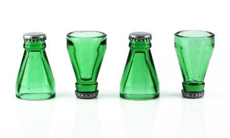 Four shot glasses in the form of tops of green bottles with caps. The upright shot glass rests on the cap.