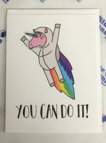 "Front of white card with illustration of unicorn with a rainbow horn in space suit with a rainbow jet pack blast. Text underneath reads ""You Can Do It!"""