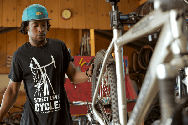 A young Black man fixing up a mountain bike in a bike shop.