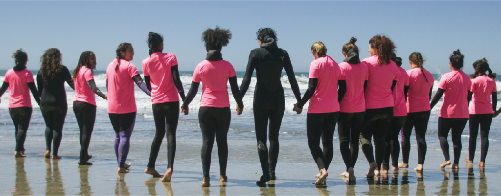 Group of women wearing pink t-shirts and wetsuits holding hands in front of the ocean