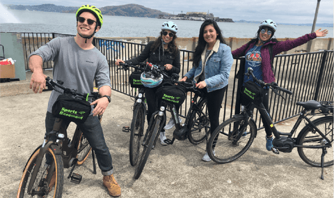 Group of people riding e-bikes in front of view of Alcatraz.