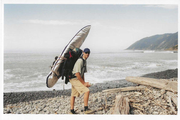 Dave Rumberg with his backpack and surfboard on a beach.