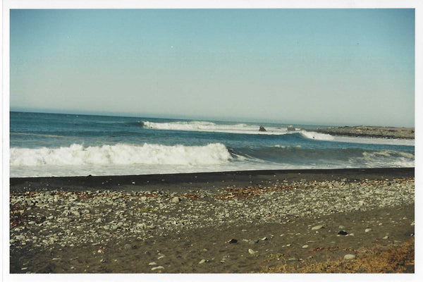 Photo of breaking waves on the beach with tiny surfers barely visible on the waves.