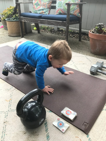 Little boy doing a push up on a yoga mat with a deck of cards next to him.