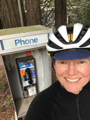 Selfie of Lynell with a telephone booth in the woods behind her.