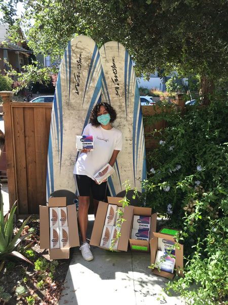 A young Black woman standing with our waffle & GU donations in boxes with two surfboards behind her.