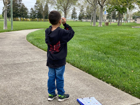 Mike's son holding his cardboard binoculars searching for items on his scavenger hunt.