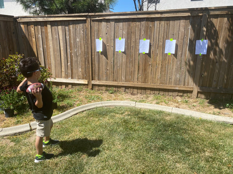 Aiden aiming a football at a letter.