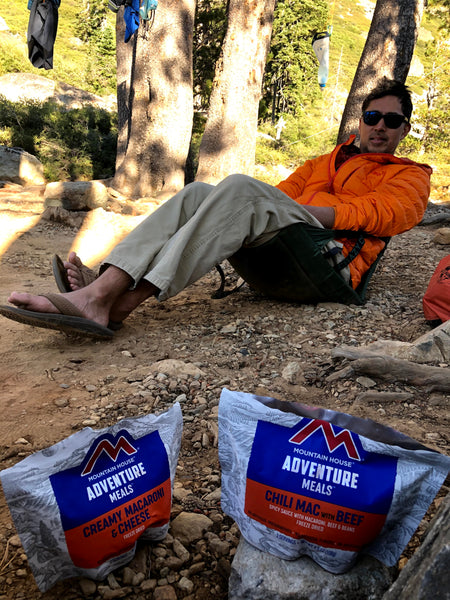 Susan's husband sitting in a camp chair with backpacking food packs