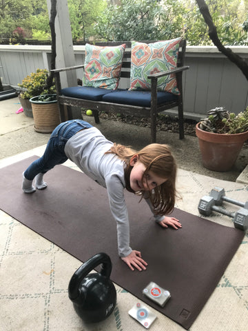Little girl doing a push up on a yoga mat with a deck of cards next to him.