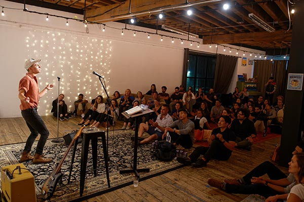 Photo of a singer performing in front of a crowd at the Bryant Street community space.