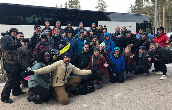 Photo of a large group in front of the Sports Basement Tahoe ski bus on a corporate retreat to the mountains.