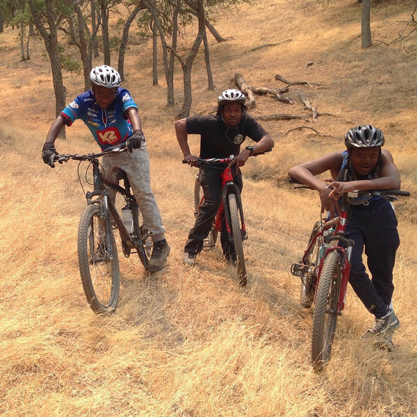 Three young Black boys mountain biking through a trail.