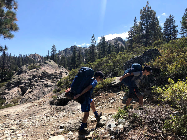 Susan's two sons wearing their backpacks and hiking.