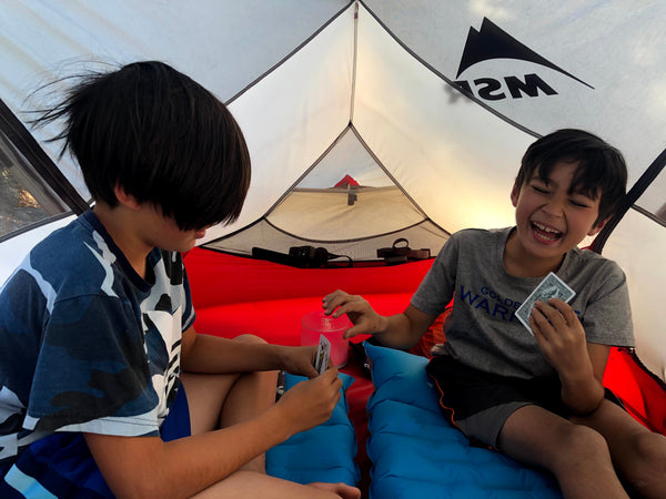 Susan's sons playing cards in a tent.