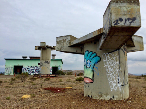 Photo of large cement bases covered in graffiti art and a green building.