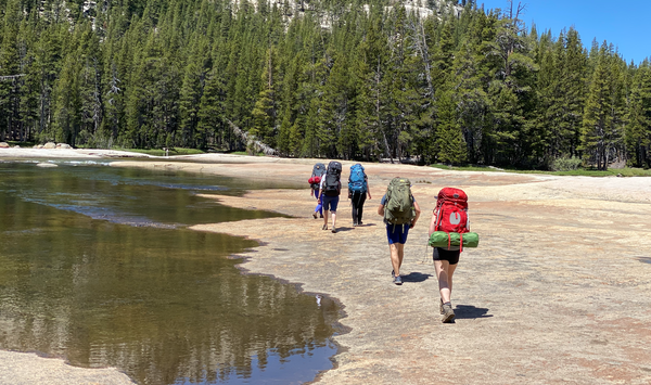 Photo of hikers along the Tuolumne River heading to Glen Aulin.