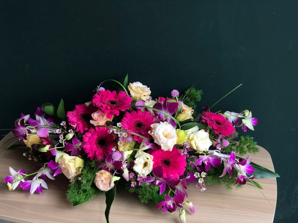 Pink Gerbera, Purple Two-Toned Dendrobium and  Champagne Eustomas Table Arrangement