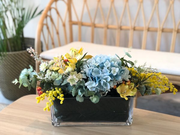 Faux Blue Hydrangeas and Yellow Alstromerias In A Long, Low Vase