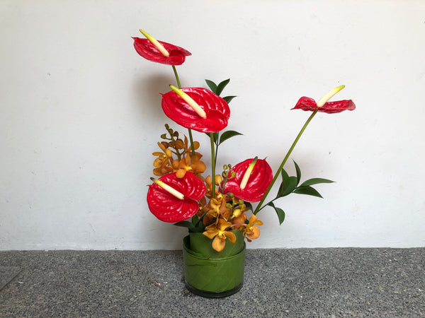 Red Anthuriums, Orange Orchids & Ruscus Cocktail Arrangement