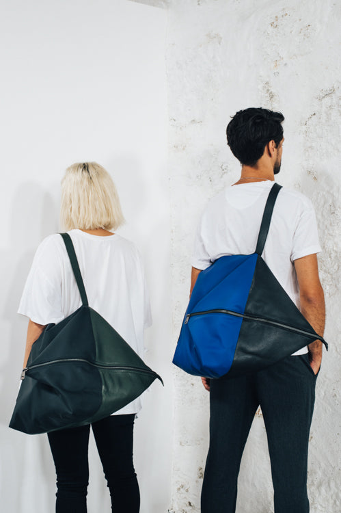 women and man with large backpack in black leather and waterproof material