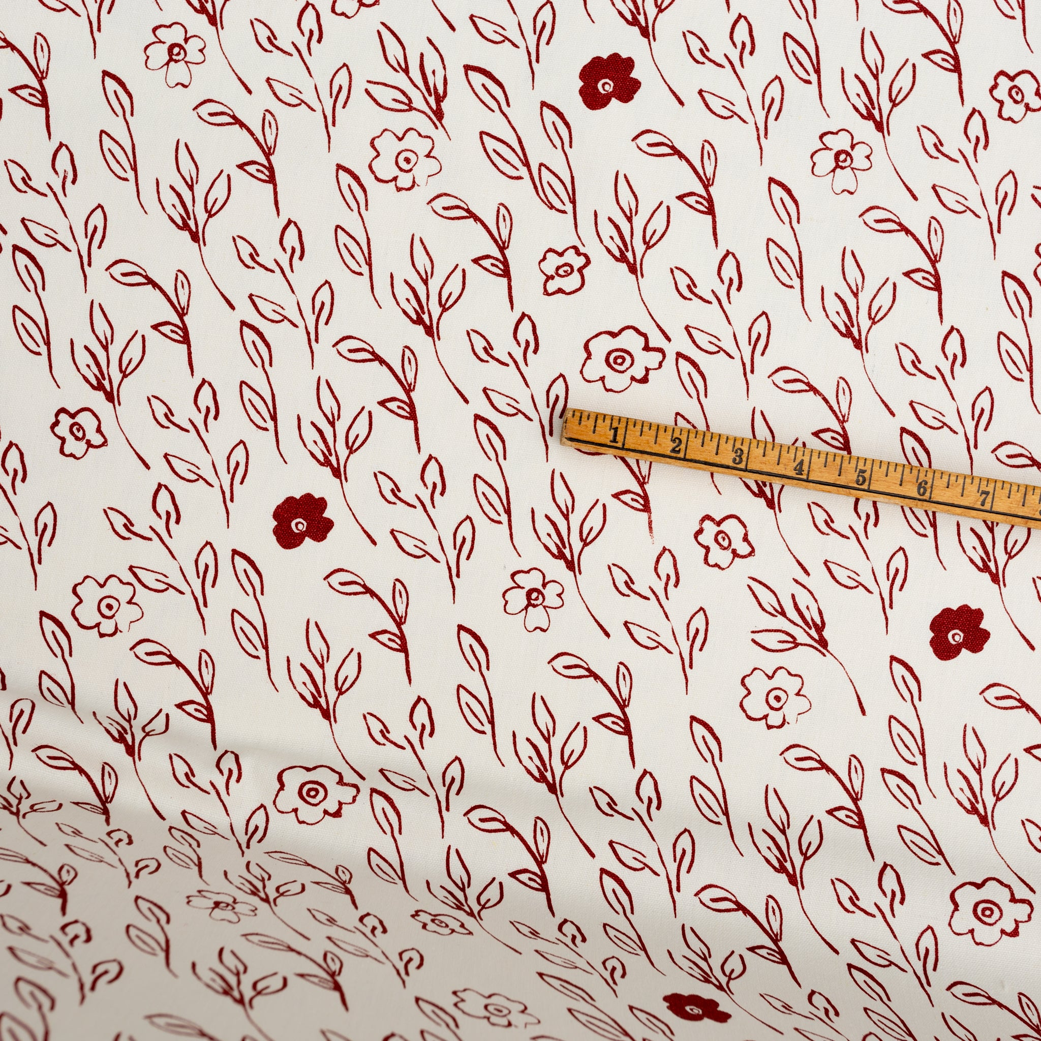 Screenprinted fabric yardage of Briar printed in Brick with yardstick