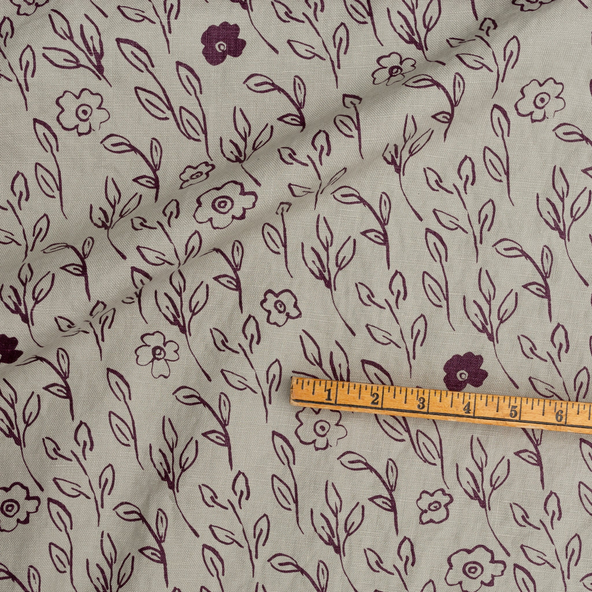 Screenprinted fabric yardage with leaves and flowers with yardstick