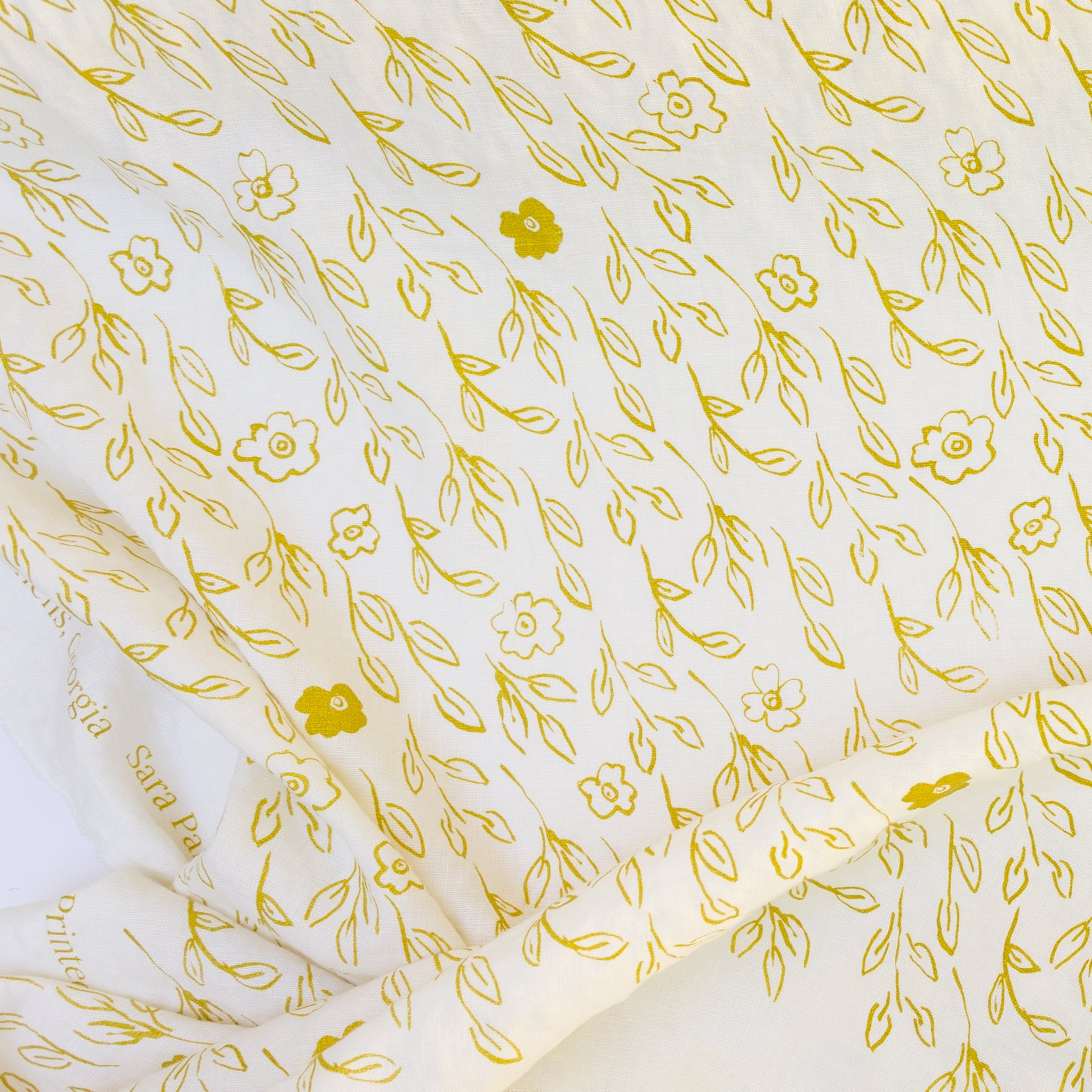 Screenprinted linen with yellow flowers and leaves by Sara Parker Textiles