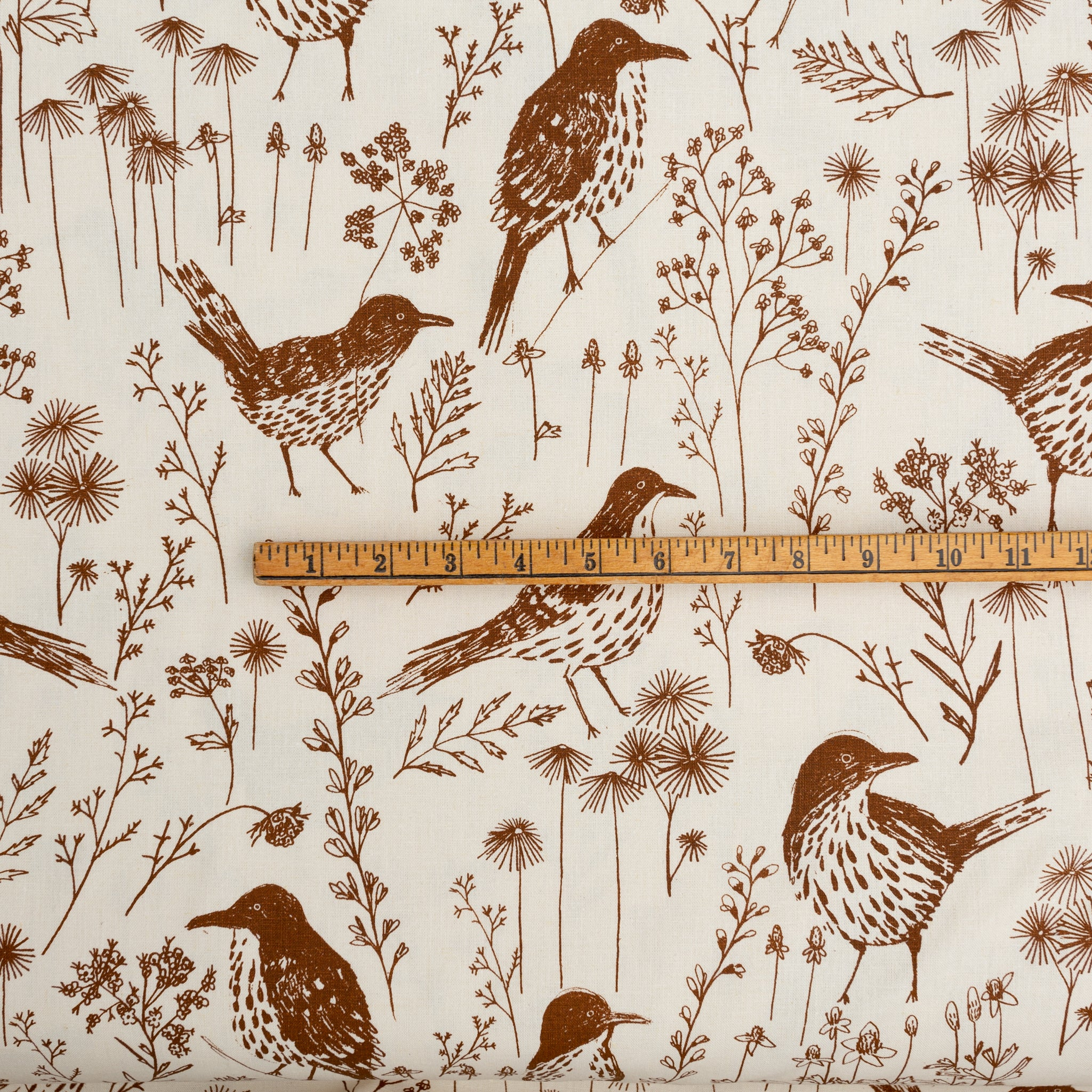 Screenprinted fabric yardage with brown thrashers and ruler for scale