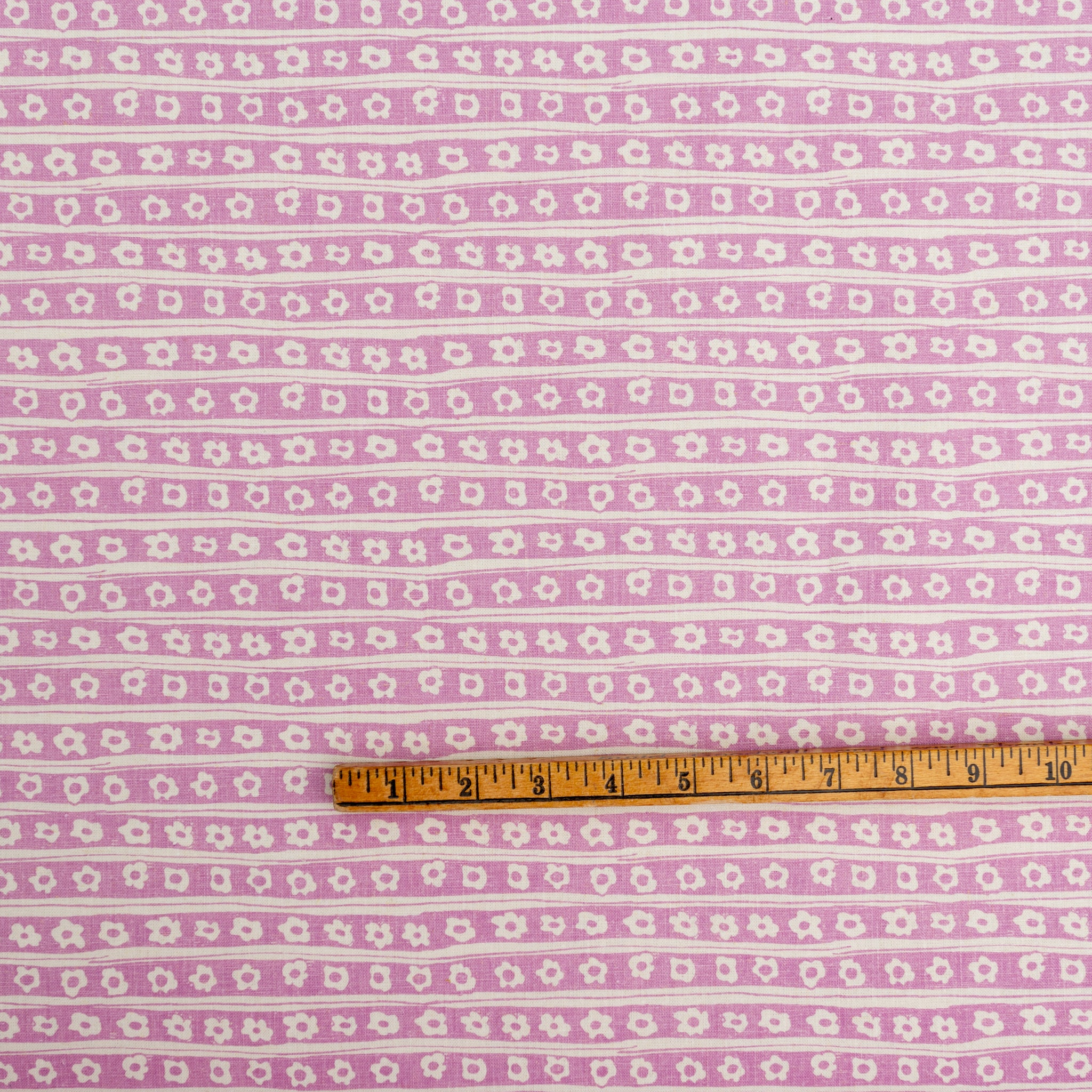 Screen printed fabric yardage with daisy pinstripes and ruler for scale