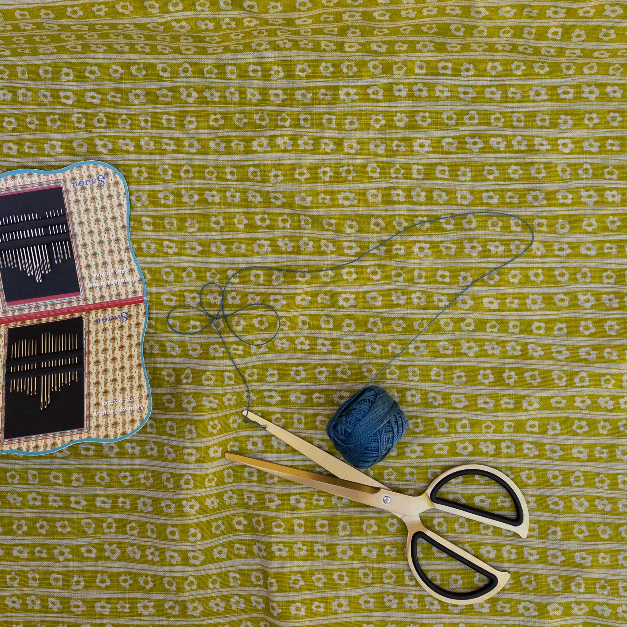 Screen printed fabric with daisy stripes shown with sewing tools