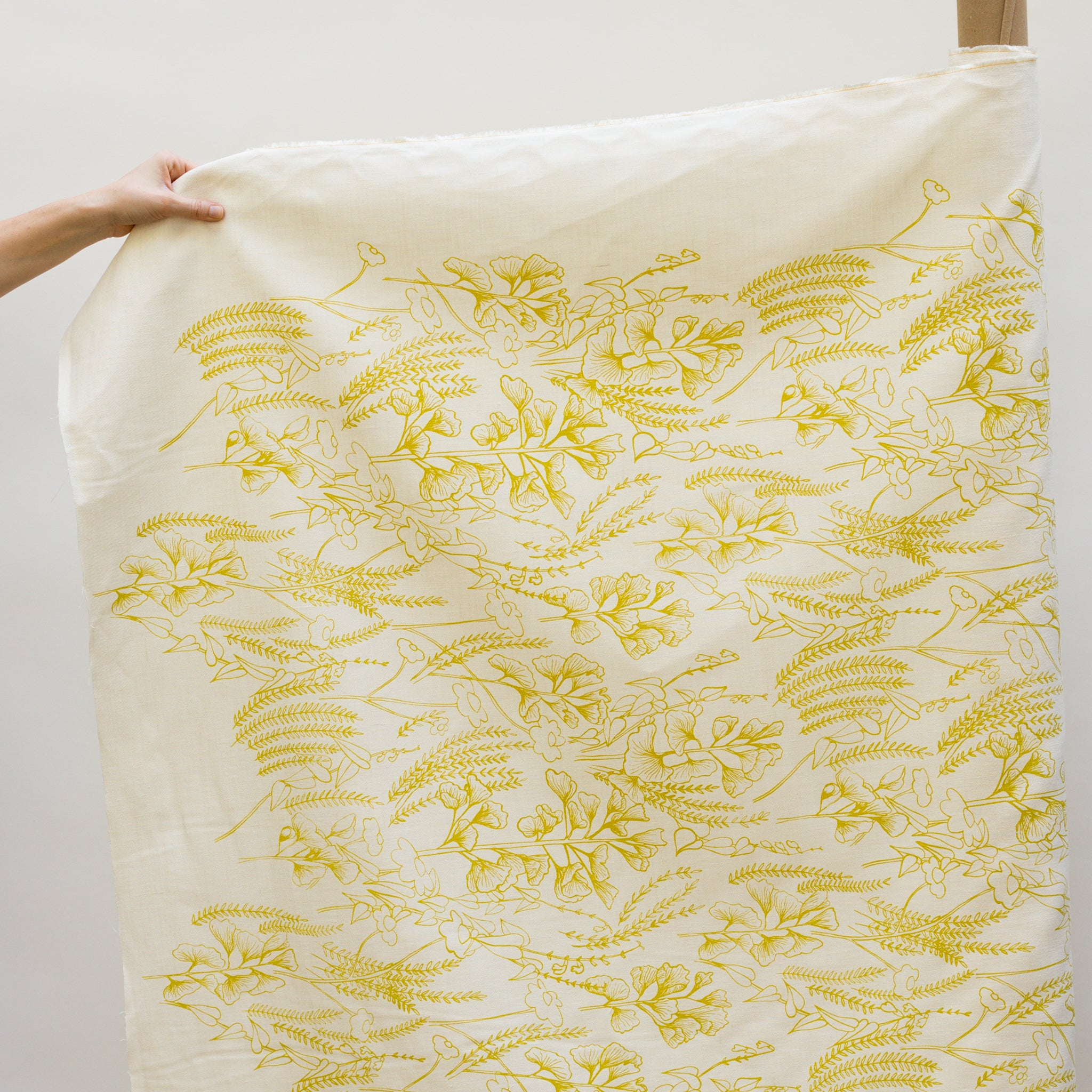 Screen printed fabric yardage of Ginkgo in Yarrow on the fabric roll with hand for scale
