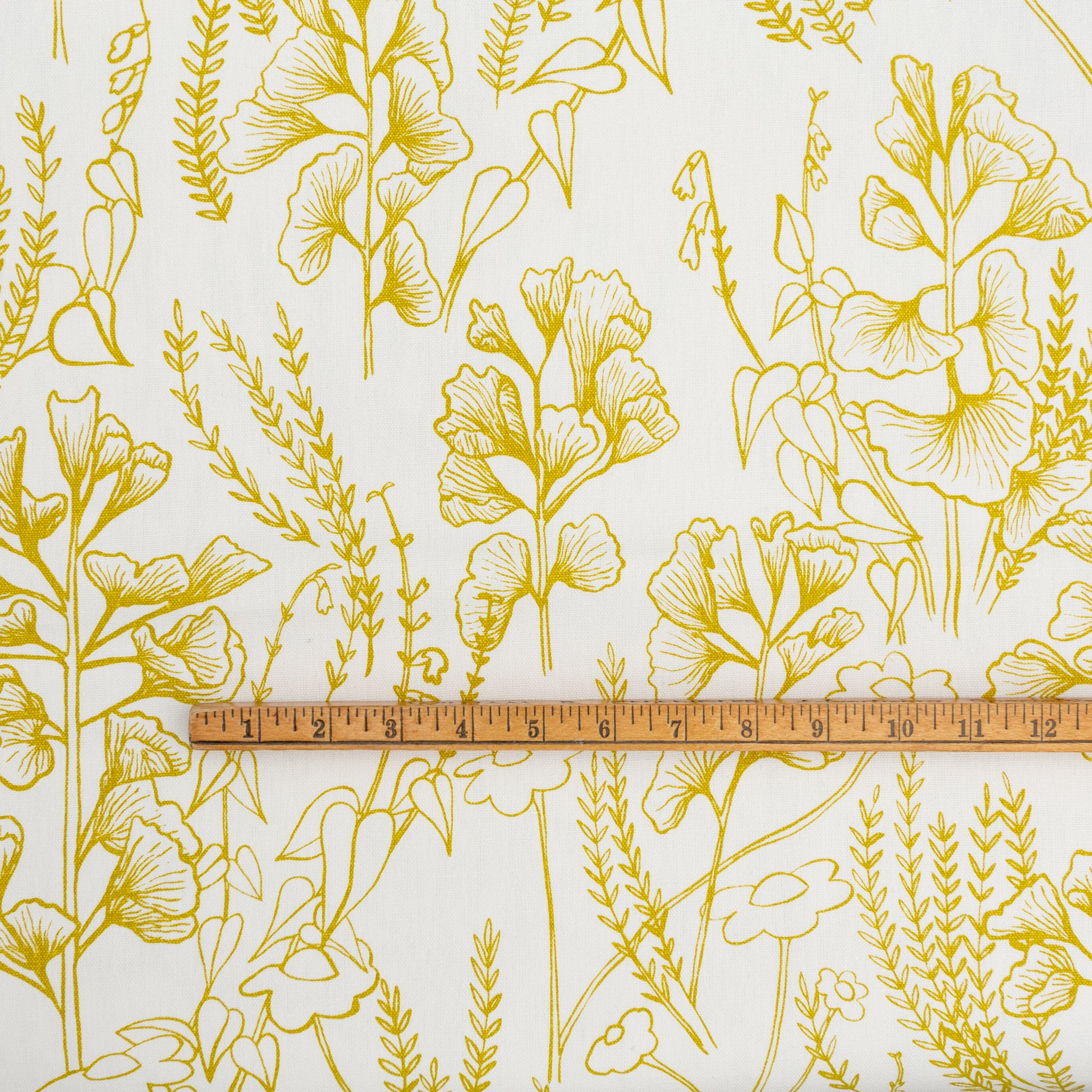 Screen printed fabric yardage with botanical illustrations and yardstick for scale
