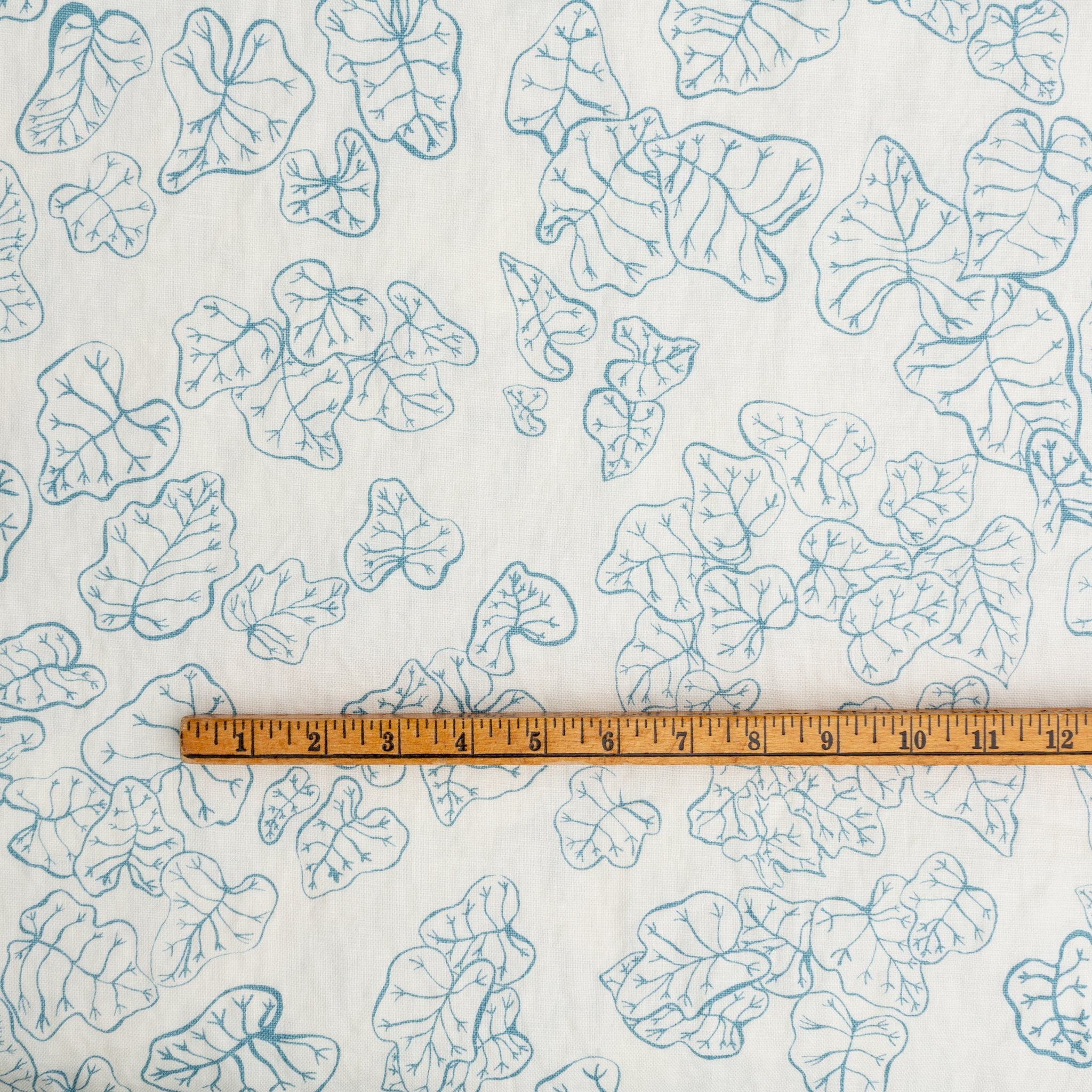 Screen printed fabric yardage with heuchera leaves with ruler for scale