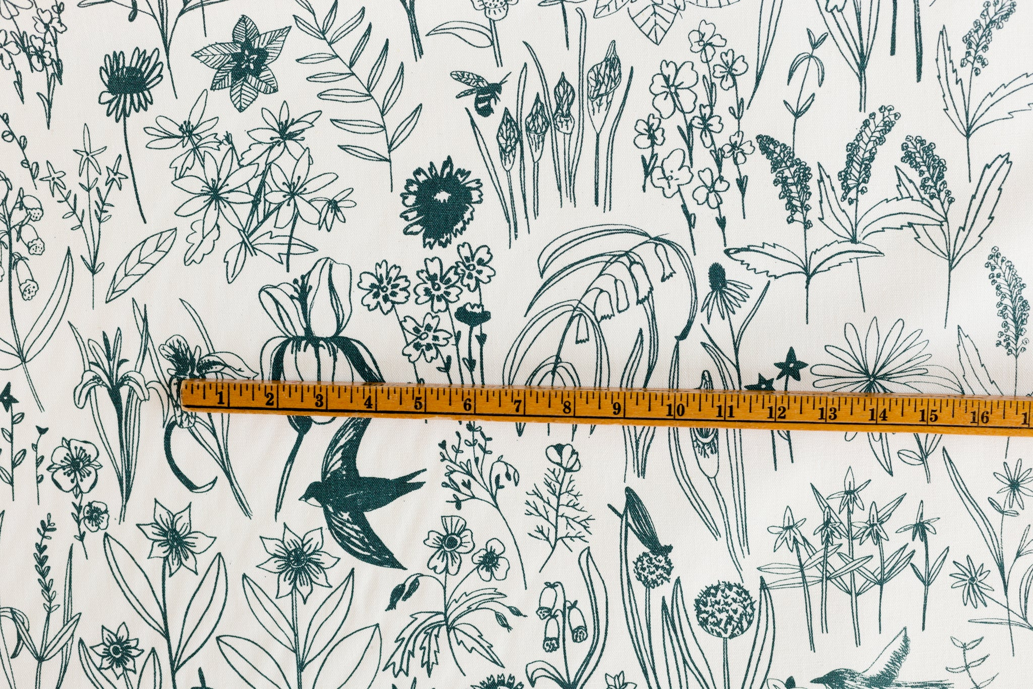 Fabric yardage screen printed with bird and botanical illustrations with yardstick for scale