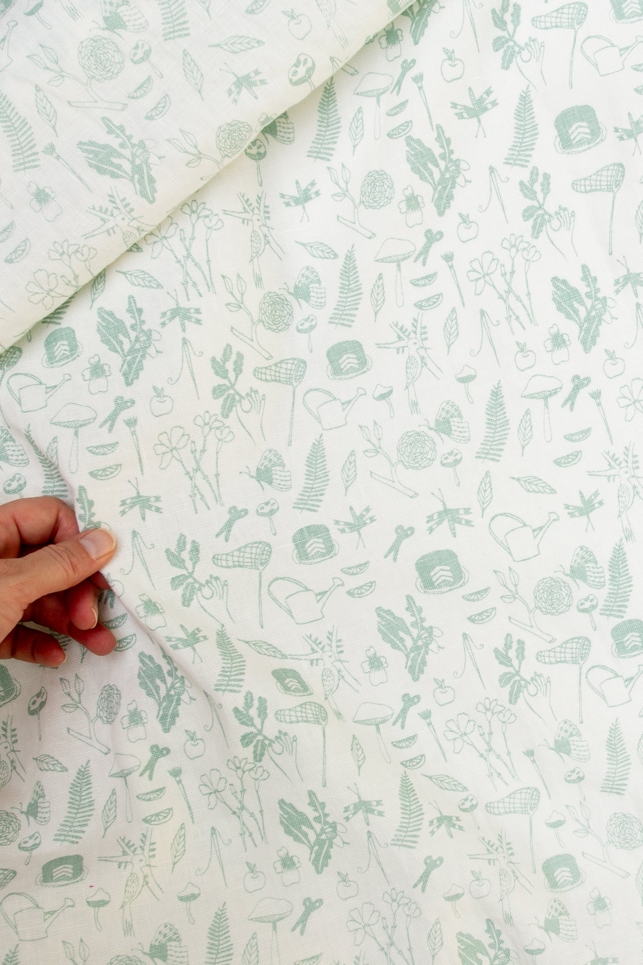 Screen printed fabric yardage with little illustration and hand for scale