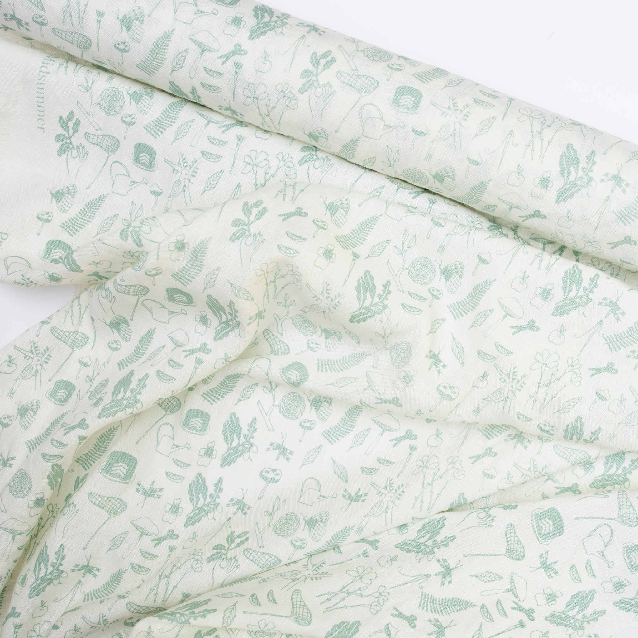 Screen printed fabric yardage with little illustrations in green
