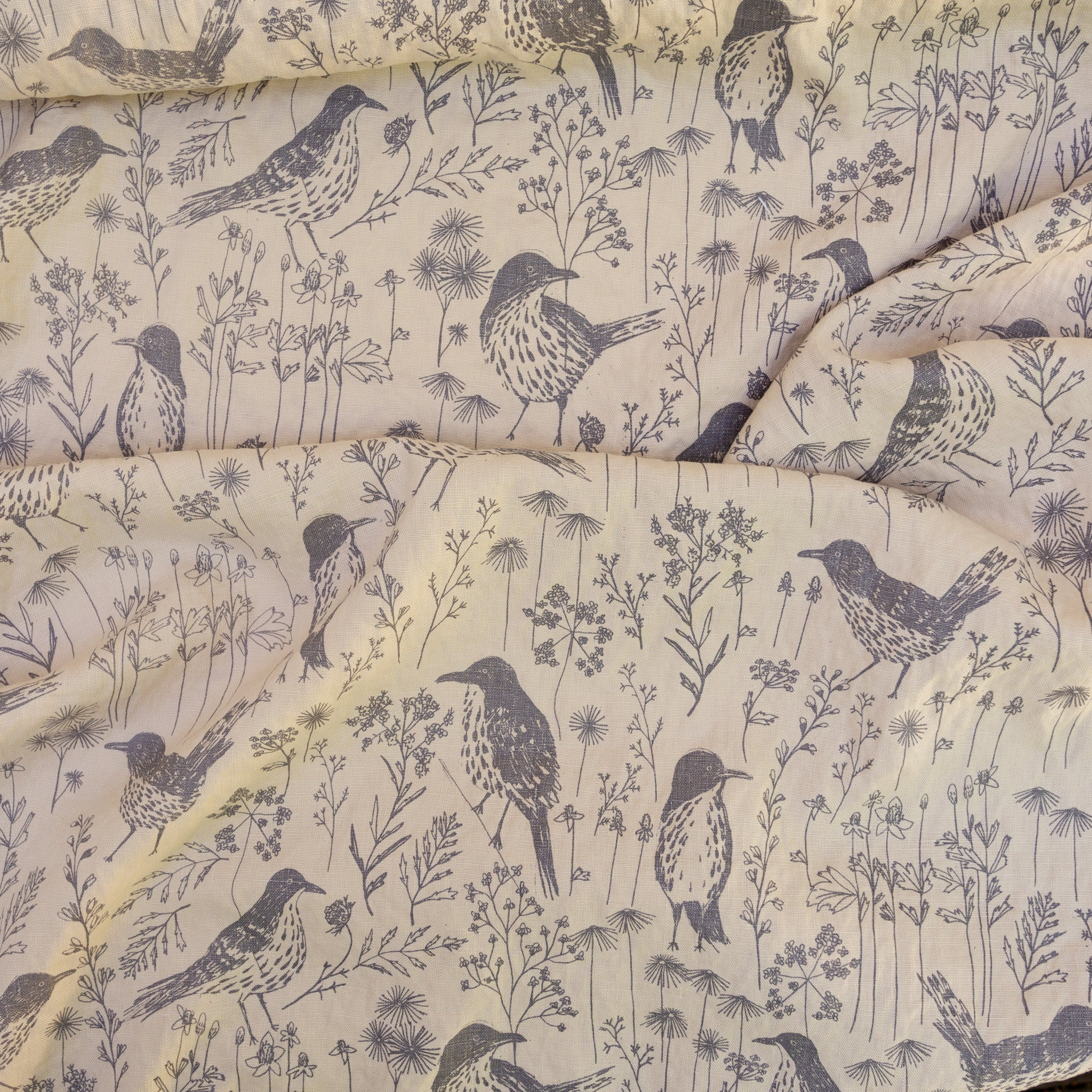 Yardage of brown thrashers screenprinted on linen