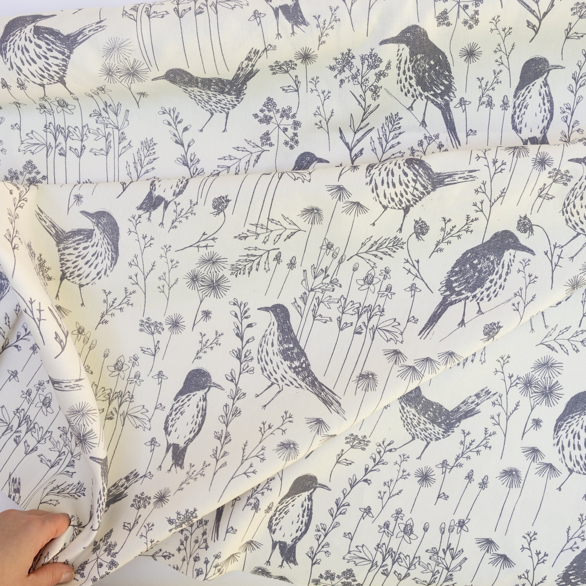 Screenprinted fabric yardage with brown thrashers and hand
