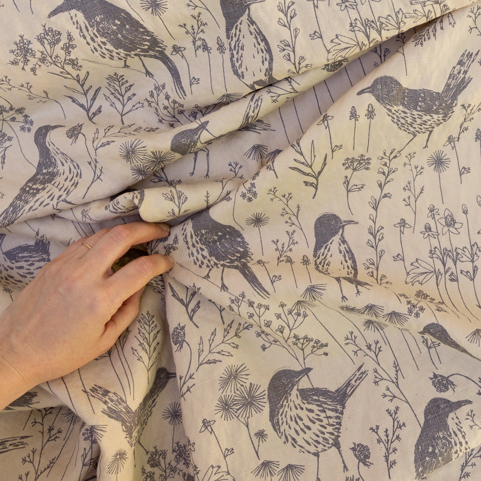 Screen printed fabric yardage with brown thrashers and hand for scale